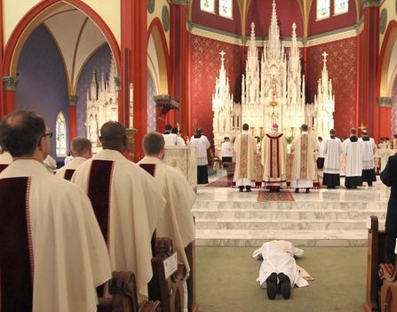 Man prostrating himself during an ordination